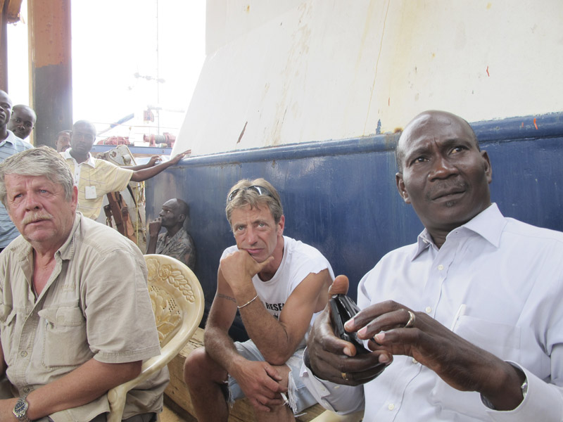 Sea Hunter owner Greg Brooks, left, and Captain Gary Esper, center, listen while Guerda Michel, CEO of Guerda Terminal Inc., speaks with dockworkers Monday afternoon at the Haitian port of Miragoane.