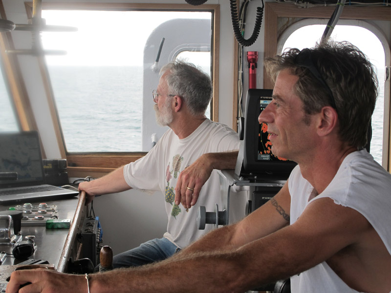 Captain Gary Esper of Hopkinton, Mass., right, and volunteer Shipmaster Kevin Garthwaite of Wells guide the Sea Hunter to its anchorage this morning off the Haitian port of Les Cayes.
