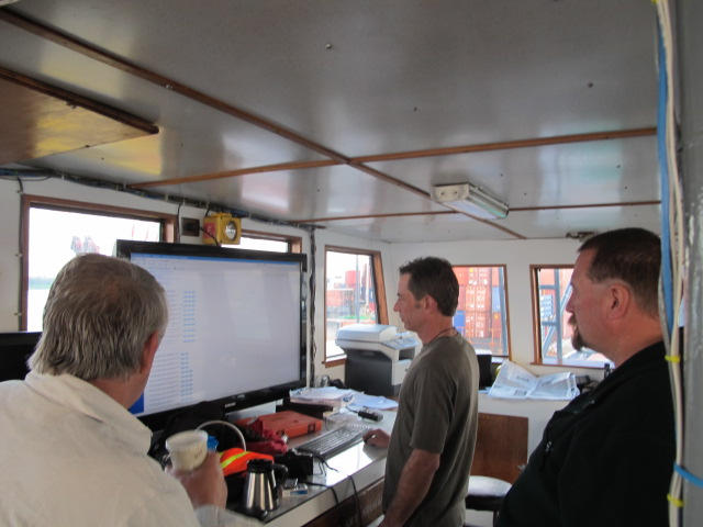 Sea Hunter owner Greg Brooks, left, checks the long-range weather forecast between Miami and Haiti on Monday along with ship captain Gary Esper, center.