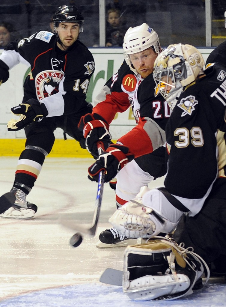 Jeff Cowan of the Portland Pirates attempts to slip the puck past Brad Thiessen, the goalie for the Wilkes-Barre/Scranton Penguins, in the Pirates' 2-1 victory Tuesday night at the Cumberland County Civic Center.