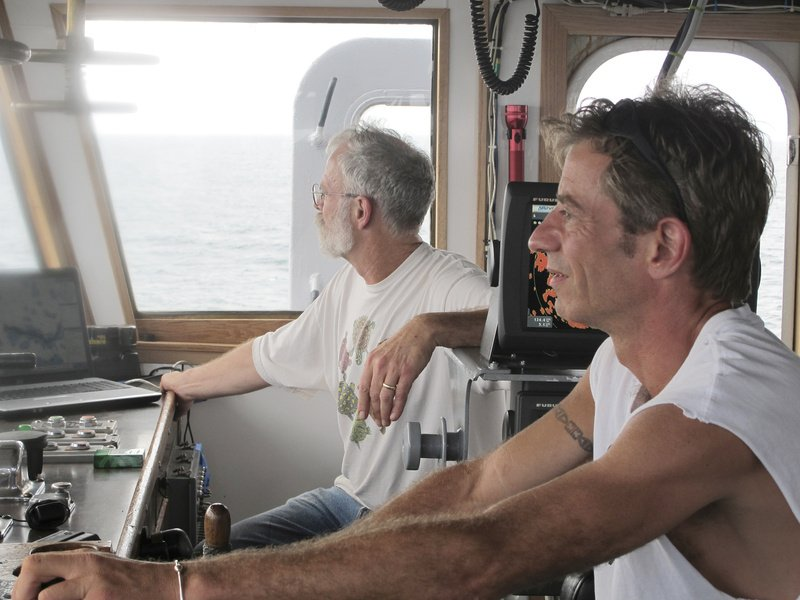 Capt. Gary Esper of Hopkinton, Mass., right, and volunteer shipmaster Kevin Garthwaite of Wells guide the Sea Hunter to its anchorage Tuesday off the Haitian port of Les Cayes