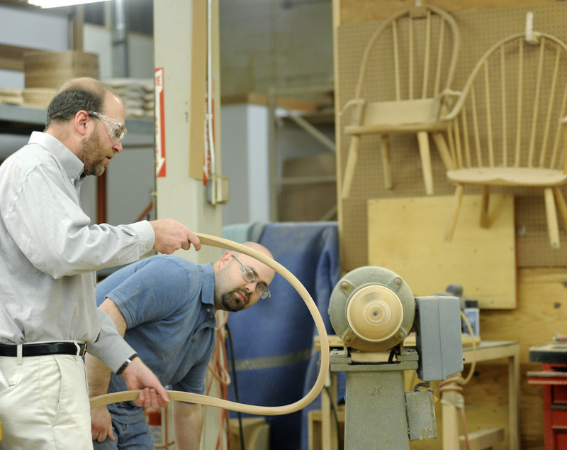 George Colby Jr., right, a cabinetmaker at Thos. Moser Cabinetmakers in Auburn, shows Ray Routhier how to sand the back of a chair.