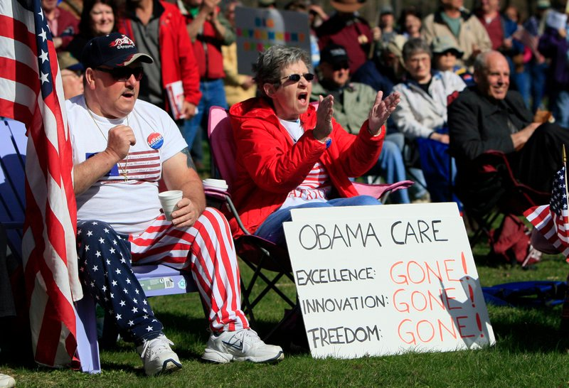 "Tea party supporters cheer during a rally Thursday at Capitol Park in Augusta, Maine. The protest featured one person dressed in colonial-era clothing and signs expressing disatisfaction with government, including a warning that ""Revolution is brewing."""