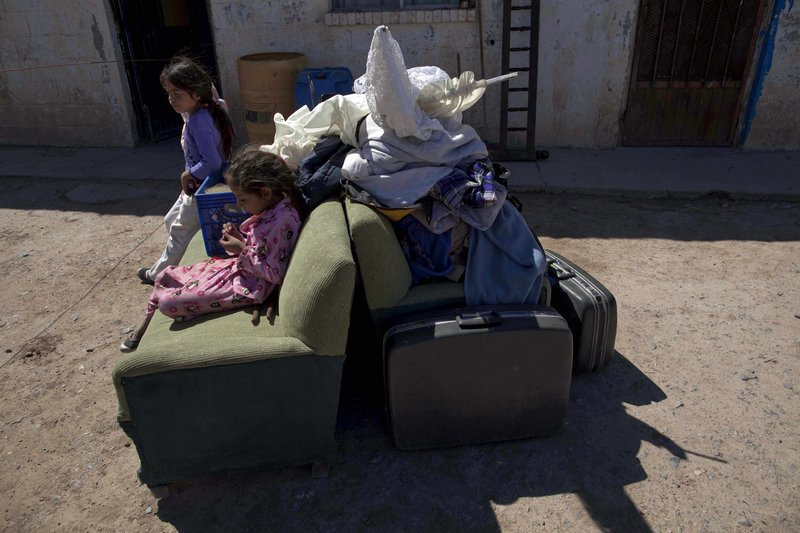 Estefania and Liliana, left, sit on their family's belongings after arriving at their new house in Valle de Juarez, on the outskirts of Ciudad Juarez in northern Mexico. The family left their home in Guadalupe after drug cartel members threatened local residents.