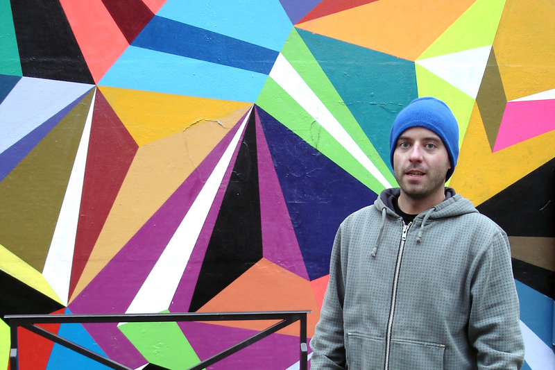"Matt Moore with one of his geometric, spray-painted designs at his ""Crystals & Lasers"" exhibition in Paris in February."