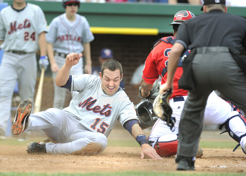 Luke Montz of the Binghamton Mets reaches to touch the plate Wednesday as catcher Juan Apodaca of the Portland Sea Dogs takes a late throw in the fourth inning of Binghamton's 10-4 victory at Hadlock Field. The Dogs are now on the road until April 30.