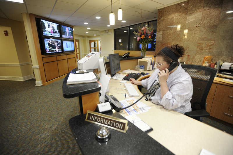 Ann Walsh answers the phone Tuesday in the Press Herald/Telegram reception area, which has four video monitors for viewing by visitors, including some that will display the media company's websites.