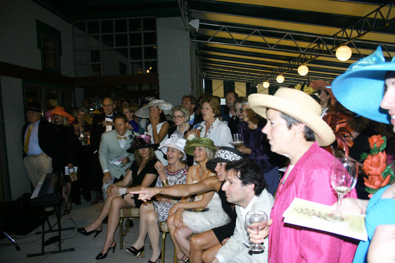 The Mad Hatter Affair centers around the Kentucky Derby, which is broadcast for the partygoers. Here the crowd reacts as Super Saver defies the muddy track and wins the 136th derby.