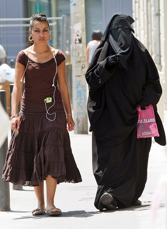 Two women on a Paris street show the difference between Western and Muslim clothing.