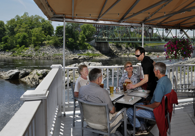 Shon Rivera, waiter at the Sea Dog Brewing Co. in Topsham, serves beverages to Jack and Judy Bauman of Brunswick and their friends Paula and Glenn Gipson. The deck has great views of the Androscoggin River.