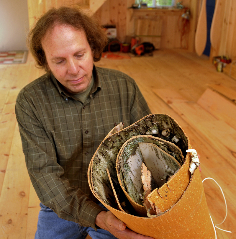 Steve Cayard shows a roll of winter bark he uses to build bark canoes. It will be soaked and used to cover a cedar frame.