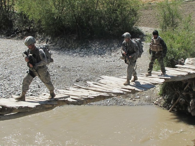 Soldiers from Bravo Company's First Platoon and a member of the Afghan Border Police cross a rickety bridge Saturday near the Afghan village of Meydani.