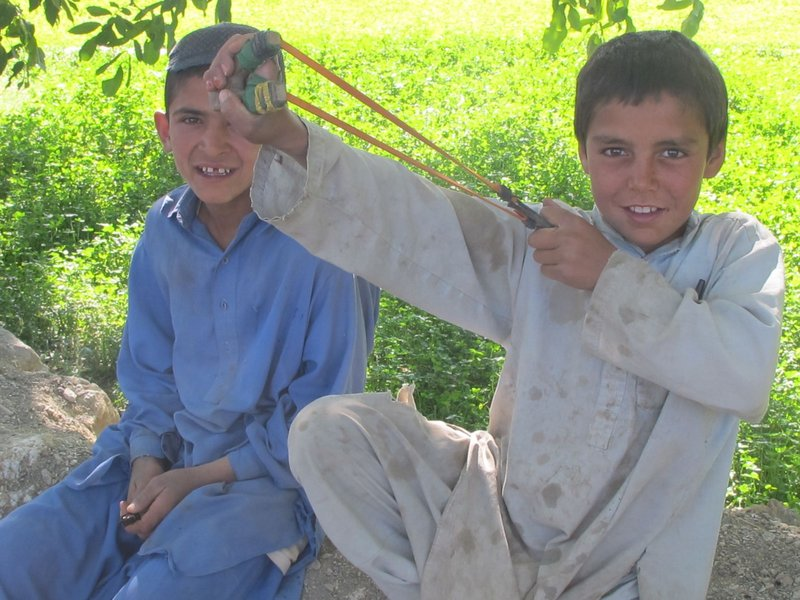 A young Afghan boy shows off his slingshot while he and his friend visit with Bravo Company soldiers Saturday outside Meydani.