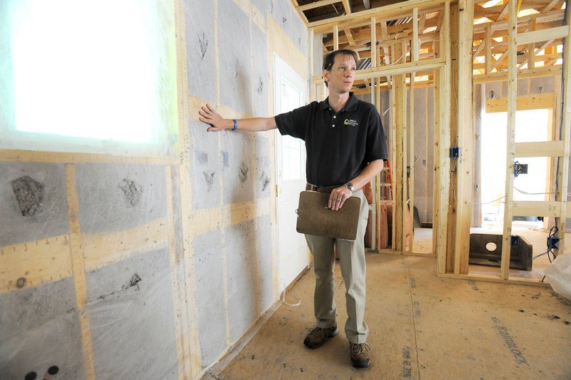 Jerry Brown, assistant manager at Quality Insulation in Yarmouth, points out areas of a building under construction that are affected by changes in new state insulation regulations.