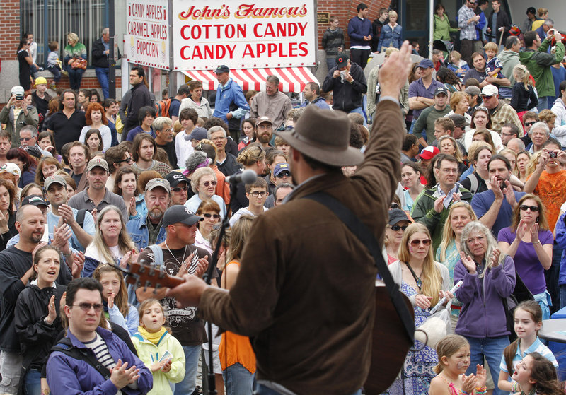 A crowd forms on the corner of Silver and Fore streets to listen to the band Gypsy Tailwind, led by Daniel Connor.