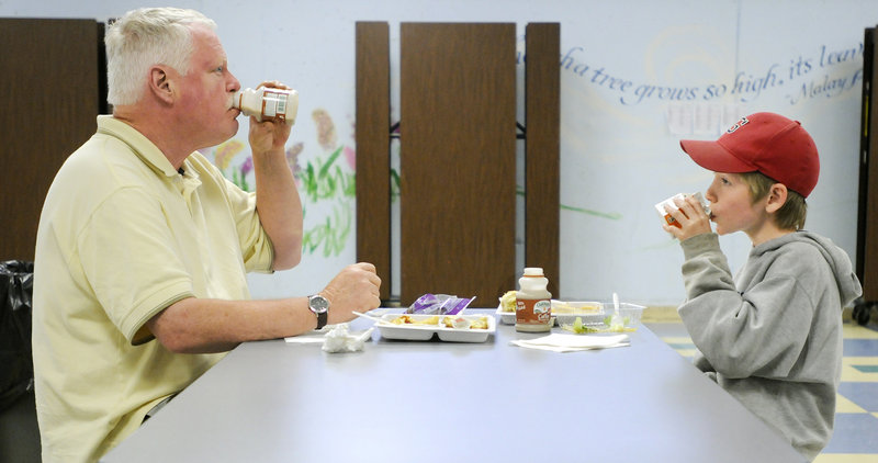 Roger Hinchliffe and his son Dana, 10, participate in the dinner program at the school.