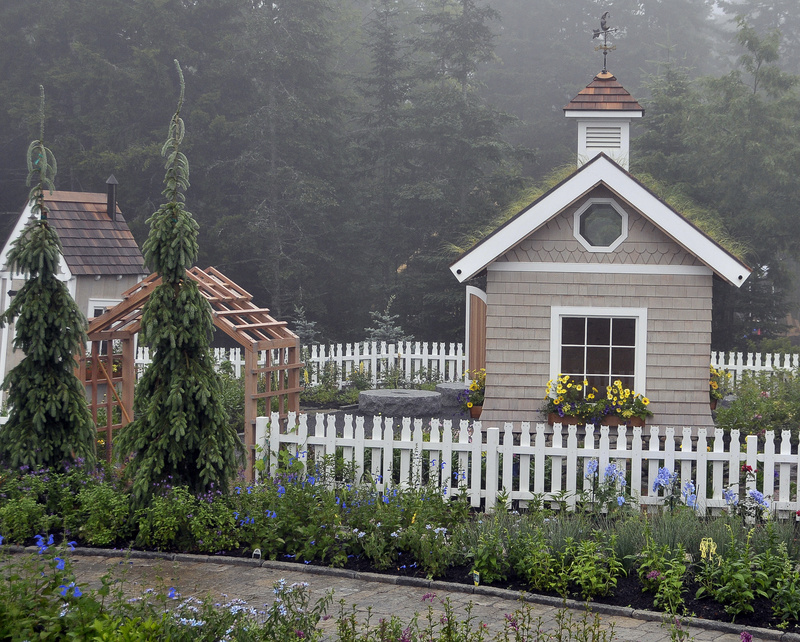A fence with a cat motif surrounds a cottage that sprouts a variety of grasses from the roof. The mission of the garden is education, and it was designed for children to have fun while learning.