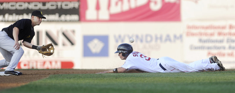 Nate Spears of the Sea Dogs makes a headfirst slide and beats a throw (ball above head) to New Hampshire's Jonathan Diaz to reach second. Spears had four hits in Portland's 11-4 win.