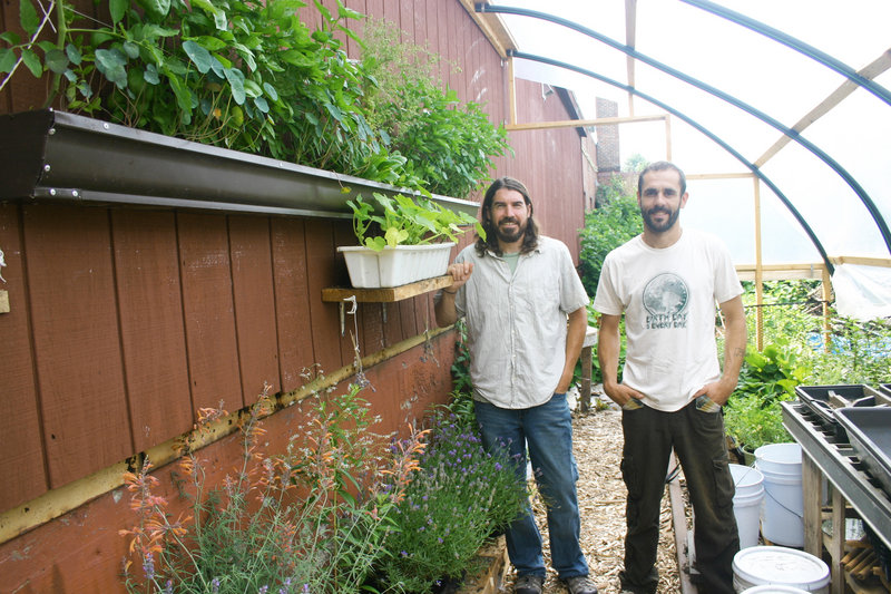 David Homa and Eli Cayer stand in the permaculture garden behind the Urban Farm Fermentory in Portland.