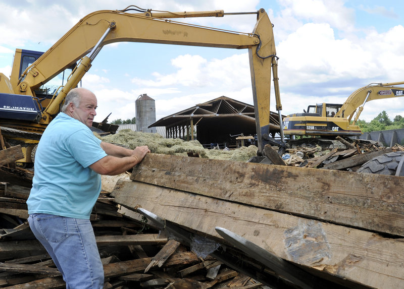 """Ed Benson salvages beams from his barn in Gorham on Thursday. The barn collapsed in a storm Wednesday night. """"It's another day on the farm,"""" said Ed Benson. """"When you live on a farm, you understand these things happen."""""""