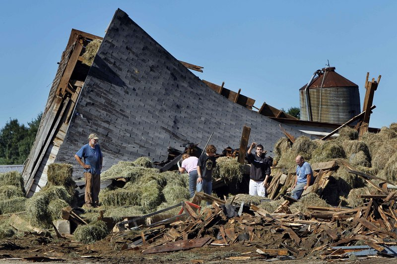 Workers and neighbors help clear debris from a barn destroyed by a severe storm at the Benson dairy farm in Gorham on Thursday.