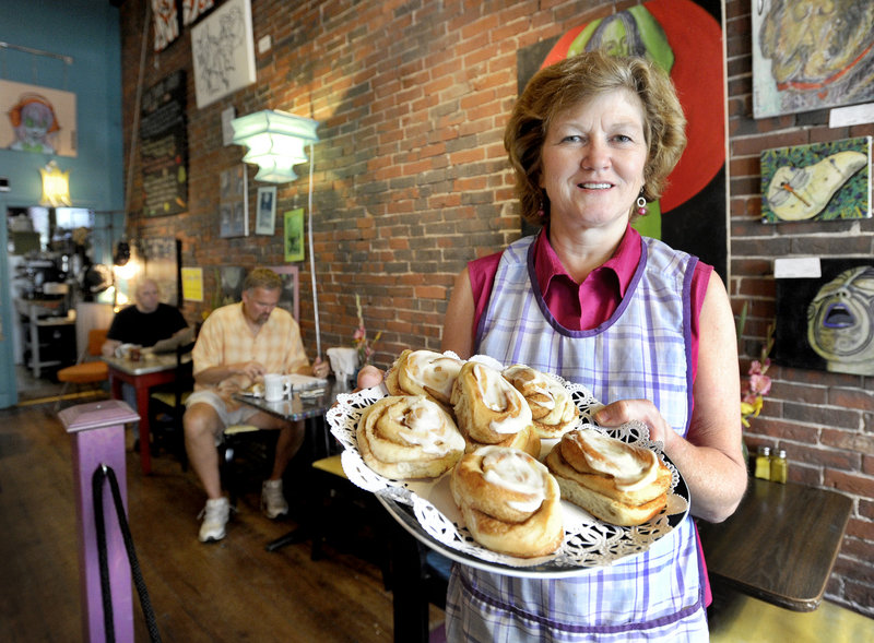 Linda Converse offers a trayful of cinnamon buns Monday at Oh Baby Cafe, the Biddeford restaurant she owns and operates with her daughter Ellen. The Converses, responding to increasing demand for morning meals, launched a full breakfast menu this week.