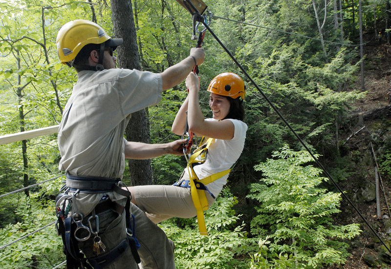 Brian Stack, a lift mechanic at Sunday River, catches Darcy Liberty as she glides onto a ramp. Such forest zip lines have long been popular in other countries.