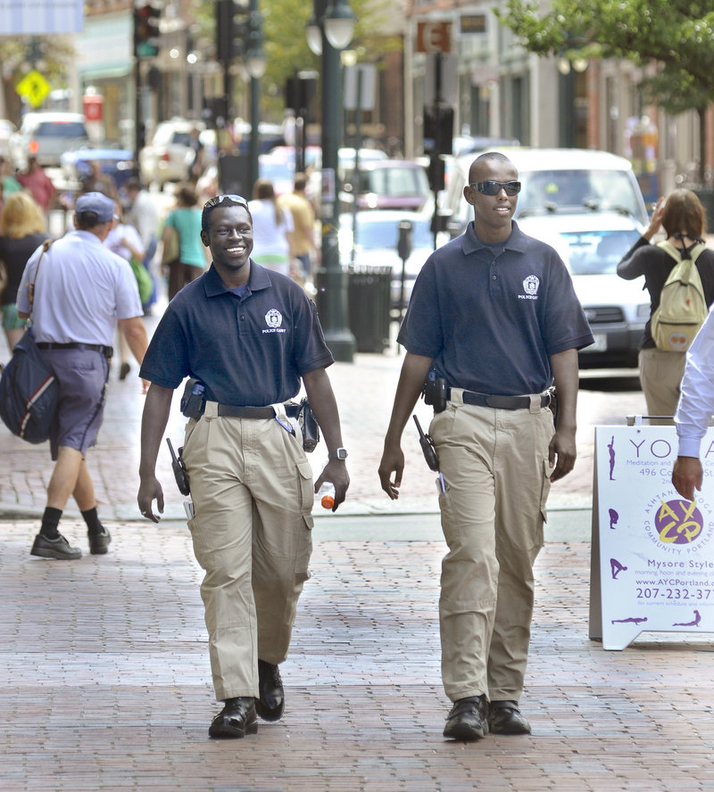 Portland police cadets Ater Ater, left, and Iman Ali patrol Congress Street in Portland on Friday. The cadets, who are interested in law enforcement careers, serve as intermediaries between police and the community.