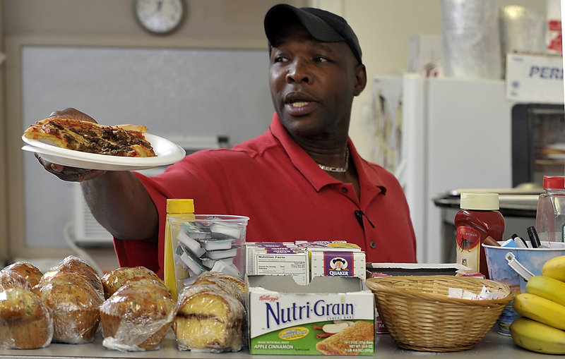 Milton Hammith, the cook at the Clock Tower Cafe, serves up a slice of pizza to a regular customer.