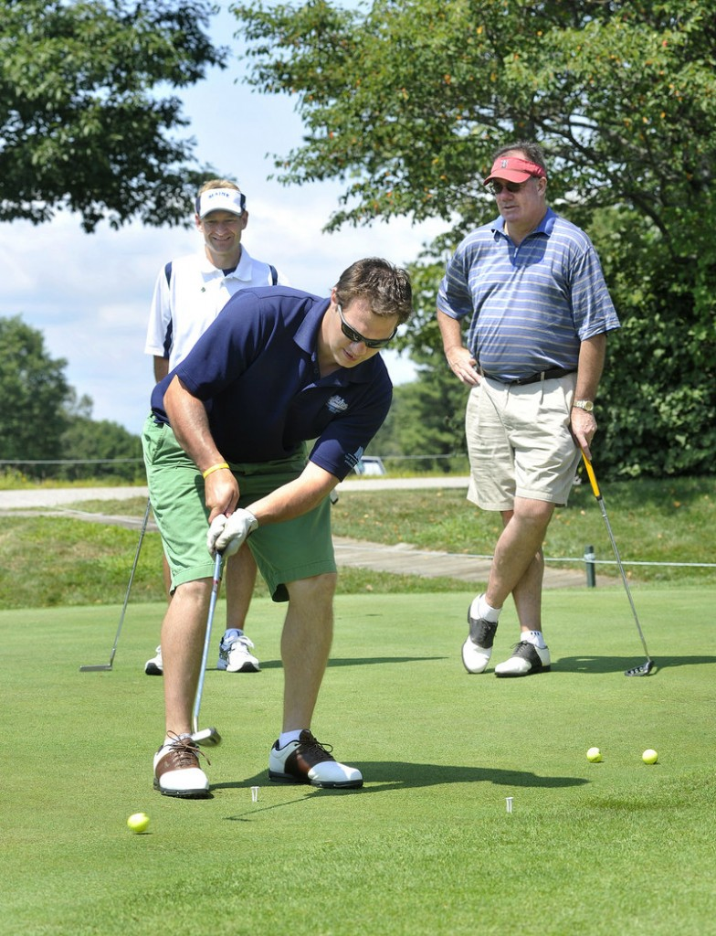Peter Metcalf, the last Maine hockey captain under Shawn Walsh, participates in a putting contest.