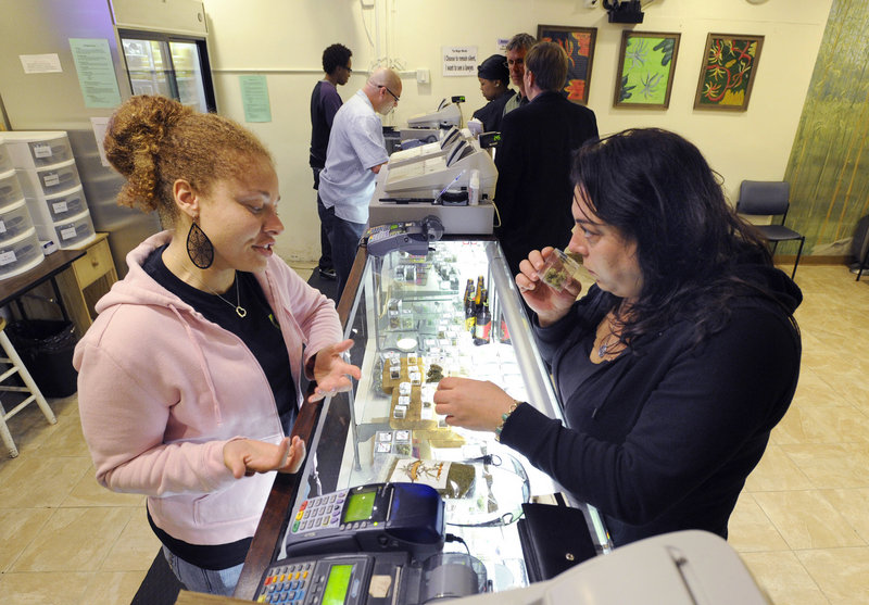 Grey, a clerk who asked that her last name not be used, helps patient Sara Romano select some marijuana at the Berkeley Patients Group clinic in Berkeley, Calif.