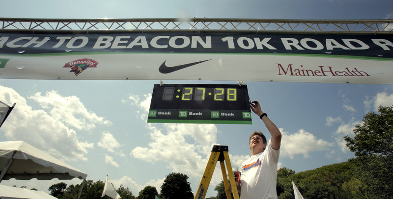 Steve Bedsole turns off power to a race clock at the finish line of the TD Bank Beach to Beacon 10K. The time of 27 minutes, 28 seconds is the course record.