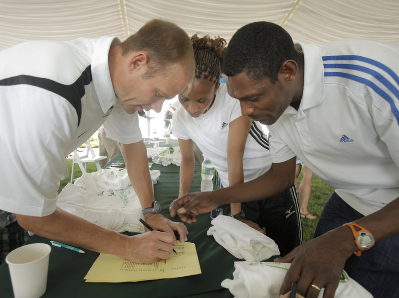 Dave Weatherbie, left, works with the husband-and-wife running team of Ayelech Assefa, center, and Dejene Berhanu after a press conference Friday leading to the running of the TD Bank Beach to Beacon 10K today in Cape Elizabeth.