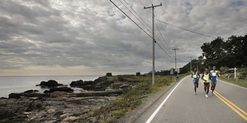 Under cloud-filled skies, the lead pack of elite runners dashes past Pond Cove along Shore Road in Cape Elizabeth during the TD Bank Beach to Beacon 10K road race on Saturday.