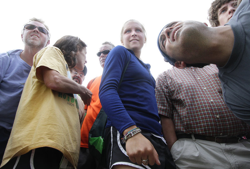 Emily Attwood, 18, of Cape Elizabeth, center, checks for results after the TD Bank Beach to Beacon 10K on Saturday.