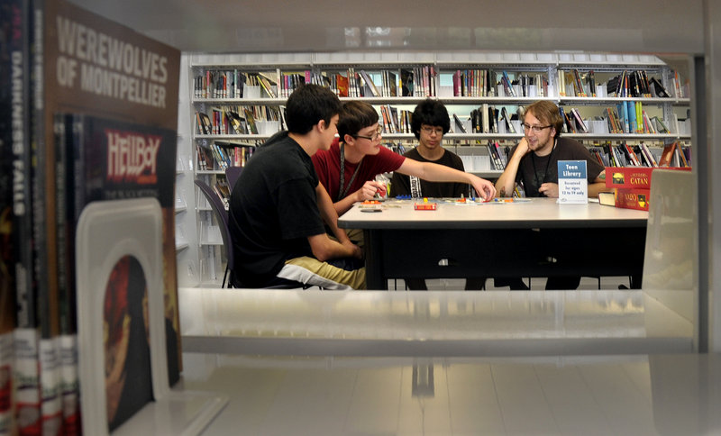 The Portland Public Library's teen librarian, Justin Hoenke, right, joins a group playing a board game called Settlers of Catan. The other players, from left, are Jake Tommer, 14, Kiril Sussky, 14, and Josh Tommer, 16.