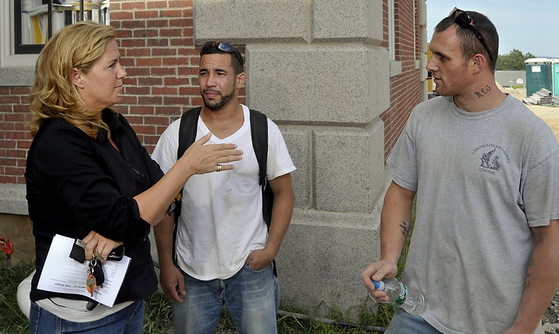 Margo Davies, who created a temp agency that specializes in finding work for felons, talks with employees Leonardo Tavares, center, and Royce Guptill at the end of a workday.