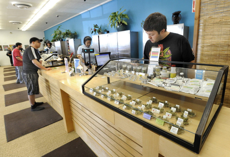 Employee Derek Flores, right, waits for a patient at a display case at the Harborside Health Center in Oakland, Calif. The center will be one of the models for Maine's first medical marijuana dispensaries.