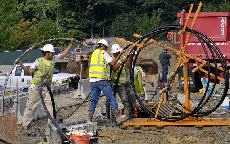 """Workers push 1,000 feet of high-density polyethylene pipe into one of 120 500-foot drilled holes that will be one """"loop"""" of the geothermal system being installed to help heat and cool the Portland International Jetport's expansion when it opens in 2012."""