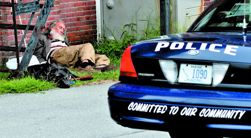 """Rod Rodriquez rests with his dog behind the Skowhegan Police Department on Monday. Rodriquez was taking a break from walking at the """"Nature Park, Nature Trails for the Homeless People of Somerset County,"""" a site located in a residential neighborhood in town."""