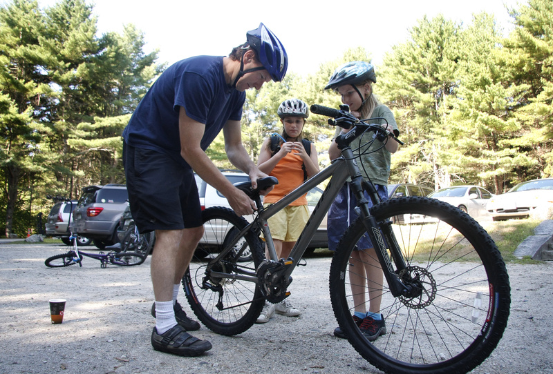 Keith McMullan of South Portland adjusts the seat for his daughter, Lydia, 11, right, as sister Izzy, 9, watches on Saturday before a ride for mountain bike beginners at Bradbury Mountain State Park in Pownal.