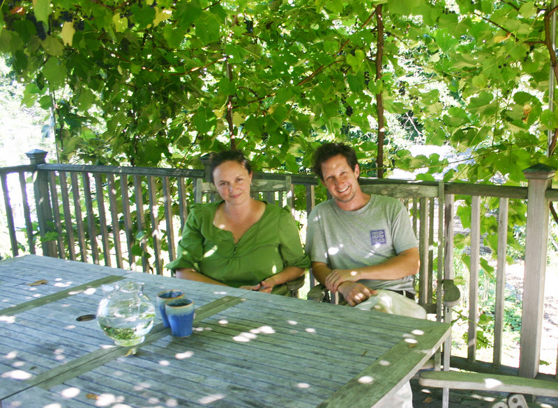 Lisa Fernandes and her husband, David Whitten, sit on their deck in Cape Elizabeth in the dappled sunshine created by the grape arbor loaded with Bluebell and Beta grapes.