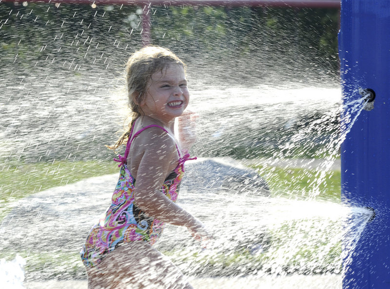 Four-year-old Makeena Wheeler of Portland lets the sprinklers cool her off at the Payson Park playground in Portland on Tuesday as temperatures surpassed 90 degrees for the third consecutive day.