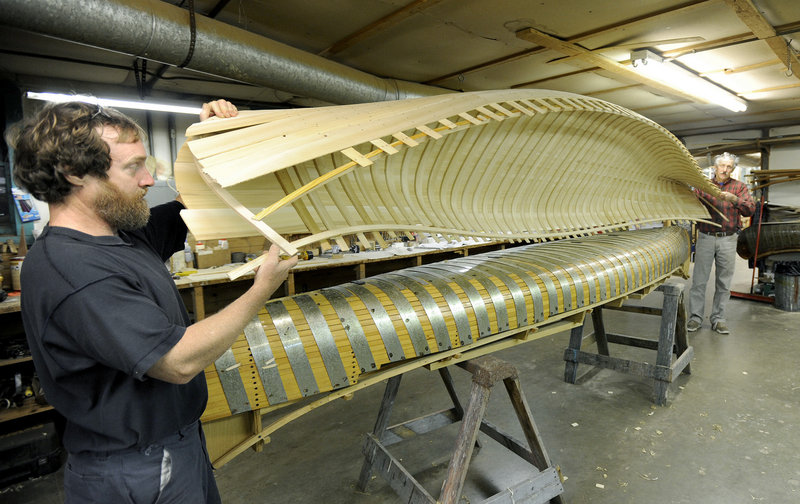 Canoe builder Jonathan Minott helps Jerry Stelmok, owner of Island Falls Canoe, lift a new canoe off its mold for continued construction. The molds for a canoe designed in the late 1880s still sit in Stelmok's workshop.