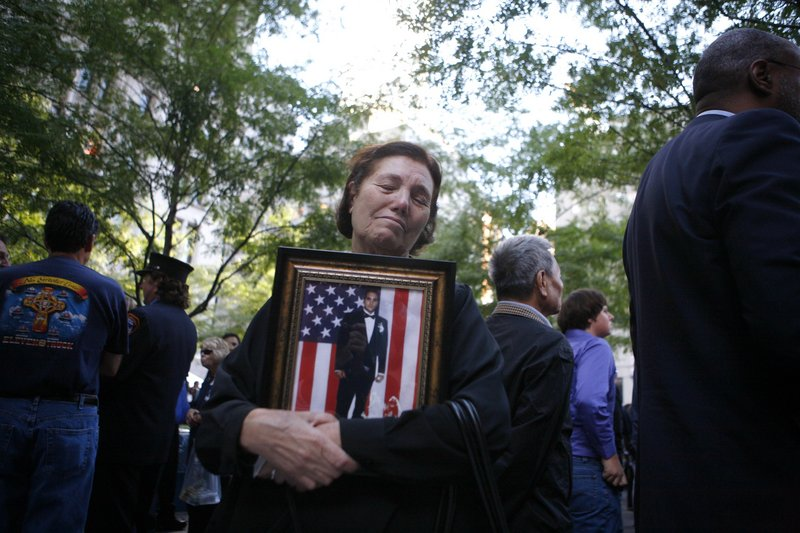 Anna Sereno of Brooklyn, N.Y., holds a photo of her son, Arturo Angelo Sereno, as friends and relatives of the victims of the Sept. 11, 2001, attacks gather on Saturday for a remembrance ceremony at Zuccotti Park, adjacent to ground zero in New York.