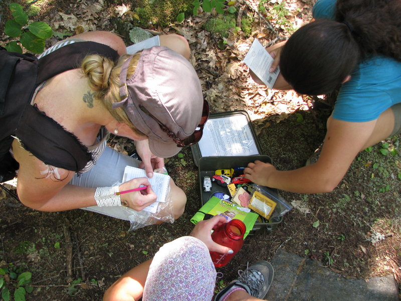 Shannon Bryan records her find in a logbook as her geocaching friends look through the cache contents.