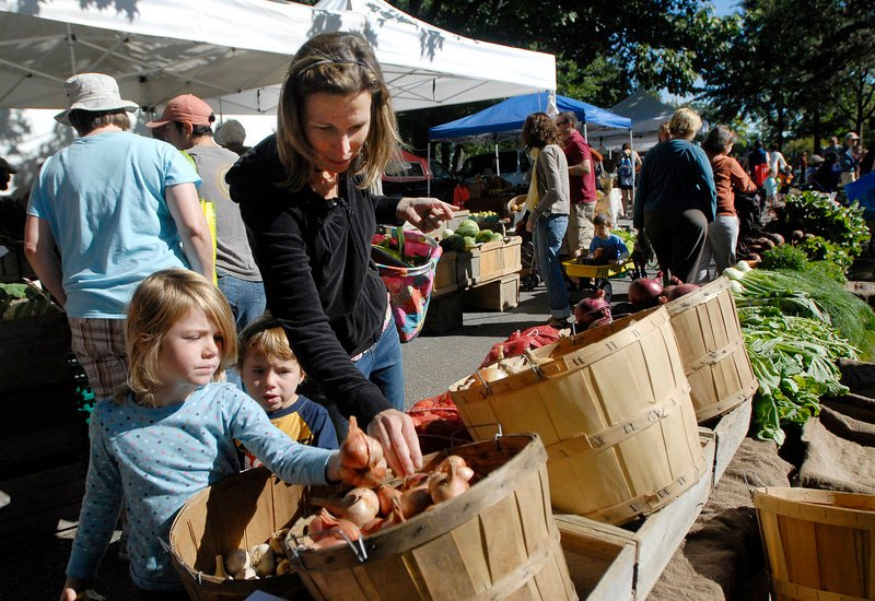 Katie Morin of South Portland gets help from her children, Abie, 5, and Ben, 3, during a recent visit to the farmers' market in Portland's Deering Oaks.