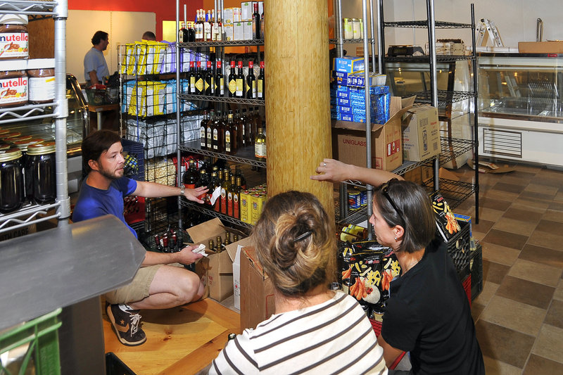 Thomas Daly, left, discusses the placement of products with Lisa Childs and Sarah Leonard in Rosemont Market's new digs. The market is doubling in size as is the bakery, which remains at the original site across Brighton Avenue.