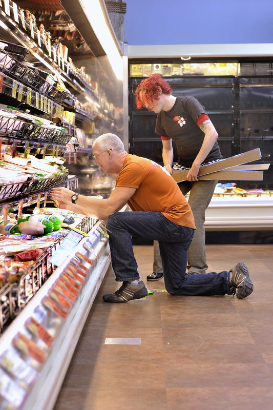 Store employees Roy Taylor (kneeling) and Elenore Toczynski place product signs on shelves as they prepare for the opening.