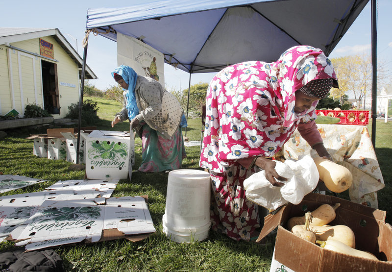 Ali and Batula Ismail, right, get squashes and other vegetables ready for sale Wednesday. They sell produce through a Community Supported Agriculture program.